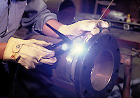 A welder doing metal repair work in the manufacturing process. machinery, equipment. California.