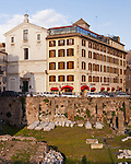 The bustle of everyday city life rises around the Imperial Forum ruins in central Rome, Italy.