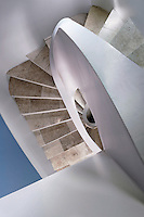 A spiral staircase with travertine steps designed by Guy Roisse runs through the middle of the 3-storey house