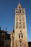 Low angle view of Giralda Minaret, Seville Cathedral, Andalucia, Spain, pictured on December  27, 2006 in the winter morning light. Seville Cathedral is the largest Gothic building in the world. It was converted from the original 12th century Almohad Mosque on this site during the 16th century and the original Moorish entrance court and Giralda Minaret are both integrated in the cathedral. Inside is the tomb of the explorer Christopher Columbus (1451-1506). The Giralda is constructed of cut bricks, originally 82 metres high, now 103 metres high with the 16th century belfry added to the original tower. Picture by Manuel Cohen