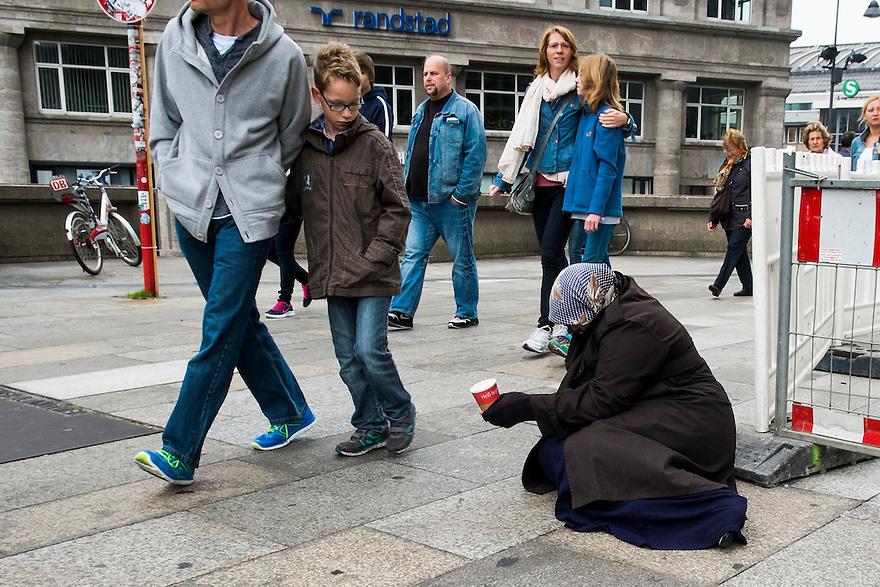 Duitsland, Keulen, 13 sept 2014<br /> Bedelares zit naast de Dom van Keulen op de grond met een bekertje.<br /> Foto: (c) Michiel Wijnbergh
