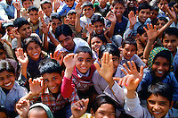 A crowd of schoolchildren waving and smiling in Nalu, Rajasthan, India
