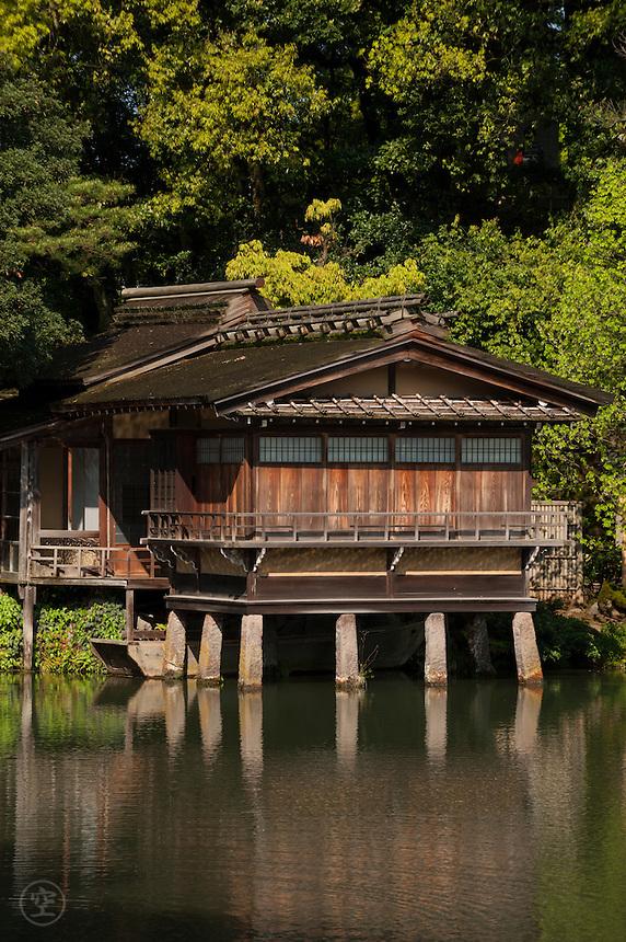 Uchihashi-tei Tea House reflected in Kenrokuen Garden's Kasumiga-ike pond on a sunny spring morning.