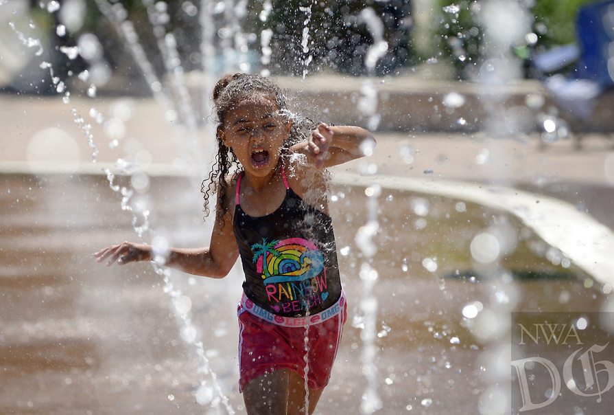 NWA Democrat-Gazette/BEN GOFF @NWABENGOFF<br /> Jaeda Davis, 7, of Jefferson City, Mo. runs through the fountains Sunday, May 14, 2017, at Lawrence Plaza in Bentonville. Sunday was the first day of the season for the fountains, which will be turned on daily from 9:00 a.m. to 10:00 p.m. through Sept. 17, except during First Fridays each month when they will be shut off at 4:00 p.m.