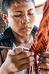 Wayuu indigenous boy in La Guajira, Colombia knitting a sash or strap.  Weaving is mostly a female profession in Wayuu communities, but some men also weave hats and textiles.