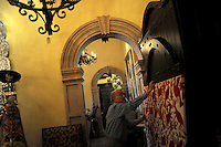 """Vega's Interiores Mejicanos"" store owner Jorge Vega moves a Mexican tapestry inside his business on August 19, 2010 in Laredo, Texas. According to Vega recent events in Mexico have severely hurt his business in Texas which has been operating on the U.S. side of the border for over 20 years (and since 1939 in Nuevo Laredo). City officials say negative attitudes about the city's more dangerous sister Nuevo Laredo have kept tourists from coming and effected the over all economics of the town."