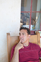 handsome middle aged man in deep thought while sitting on a chair in a porch