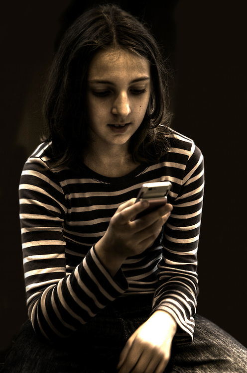 A young girl aged 11 wearing a striped top texting on her mobile phone