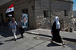 People participate in a rally celebrating Syria's independence day, showing support in its president Bashar el-Assad, in the Druze village of Majdal Shams, Golan Heights.