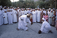 Al-Hamra, Oman, Arabian Peninsula, Middle East - Omanis perform the ar-Razha dance.  This dance is performed at weddings or, in this case, to celebrate the Eid al-Adha (Feast of the Sacrifice), the annual feast through which Muslims commemorate God's mercy in allowing Abraham to sacrifice a ram instead of his son, to prove his faith.  Spectators are wearing traditional Omani dishdashas and wearing kummas, traditional embroidered Omani hats.