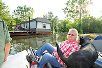 "8/11/11} Vicksburg} -- Vicksburg, MS, U.S.A. -- Mark Bridges,56, thrift store owner, and his dog ""baby girl"" and his girlfriend of 12 years Patricia Clark, a homeDepot garden employee, cruise down Chicksaw Rd in a bass boat in North Kings Community in Vicksburg Mississippi Wed. May 5th 2011. This is the firs time for Patricia to try and remove things from her trailer, that is built on 9ft stilts  AND THE WATER IS CURRENTLY AT 15 ft. and rising and is less than 12 inches from being flooded. Mark and Patricia have lived their all their lives and will return when the Mississippi River recedes,. ark has been helping his neighbors get their belongings to safety. Vicksburg a riverfront town steeped in war and sacrifice, gets set to battle an age-old companion: the Mississippi River. The city that fell to Ulysses S. Grant and the Union Army after a painful siege in 1863 is marshalling a modern flood-control arsenal to keep the swollen Mississippi from overwhelming its defenses. PHOTO©SUZIALTMAN.COM.Photo by Suzi Altman, Freelance."
