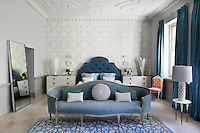 The master bedroom has soft accent colours and the decoration plays around a relaxing interaction of various layered blues. The pattern on the wallpaper and rug is different, but they both loosely mimic shapes in the ceiling plasterwork