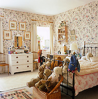 A child's bedroom with soft toys in tiers at the foot of the simple iron bedstead