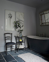 Photographs by Elena Lyakir hang in the bathroom which is furnished with a cast-iron bath and a Napoleon III chair