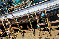 An Ecuadorian shipbuilding worker repairs the shell of a traditional wooden fishing vessel in an artisanal shipyard on the beach in Manta, Ecuador, 9 September 2012. The construction process takes 3-4 months to complete, depending on the ship size and purpose (fish capture methods). Although a wooden boat tends to be more stable on the sea and less expensive to build (up to $0.5 million USD), it needs a maintenance every 2 years, while a fiberglass-made boat, costing almost double the wooden one, may serve 5-6 years without any repairs. The shipyard produces 6-8 vessels every year.