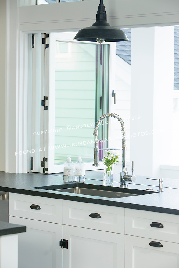 Dark stone countertops and white cabinetry create a crisp look in a newly remodeled kitchen.  This image is available through an alternate architectural stock image agency, Collinstock located here: http://www.collinstock.com