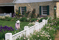 mature woman gardening in front yard garden of stone house