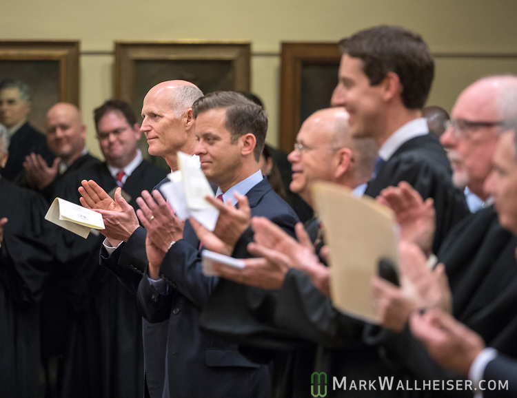 From left, Florida Governor Rick Scott, Lt. Governor Carlos Lopez-Cantera, Jonathan Sjostrom, Chief Judge of the second judicial circuit, judge Fredrick Lauten, applaud after the National Anthem during the investiture of the Honorable Alan Lawson as the 86th Justice of The Supreme Court of Florida in Tallahassee, Florida