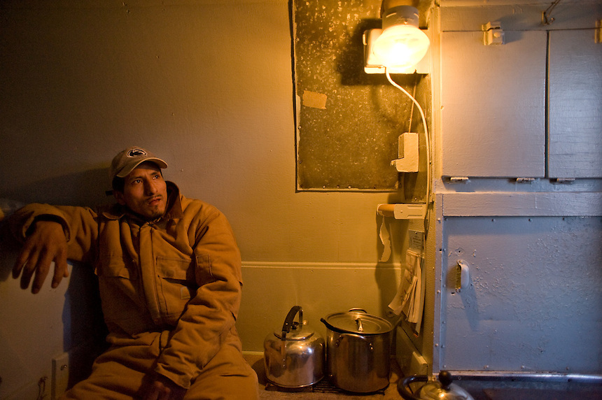 "A Peruvian sheep herder talks under gas light in the cramped quarters of his ""campito,"" or horse-drawn camp wagon, on Bureau of Land Management land near Rock Springs, Wyo., Saturday, Feb. 7, 2009. Sheep herders working in southern Wyoming along the Colorado border complain of low pay, poor accomodations and lack of health care after they arrive on H2A visas to work for local ranchers. (Kevin Moloney for the New York Times)"