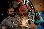 Mohammed Gull, left, his son Asad Ullah, center, and apprentice Bashir, right, work in Gull's Kabul, afghanistan bike shop. The shop earns about $4-6 USD per day.