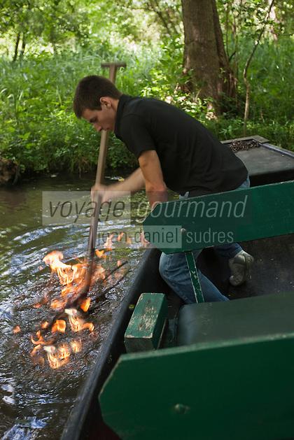 Europe/France/Poitou-Charentes/79/Deux-S&egrave;vres/Sansais/La Garette:  Promenade en barque  plate  localement d&eacute;nomm&eacute;es:&nbsp;batais avec batelier-guide,Le batelier montre:  Le feu sur l&rsquo;eau  .On enflamme les bulles de m&eacute;thane qui proviennent de la fermentation des v&eacute;g&eacute;taux . Au fond du foss&eacute; <br /> ans le fond des canaux, les d&eacute;bris v&eacute;g&eacute;taux s'accumulent. Leur d&eacute;composition lente produit du m&eacute;thane, un gaz inflammable . En agitant la vase avec leur pigouille, le gaz est lib&eacute;r&eacute;. Il remonte &agrave; la surface de l'eau et il est tr&egrave;s facile de l'enflammer.  [Autorisation : 2011-118]
