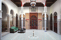Ground floor central courtyard with a fountain in the centre, zellige tile decoration and painted door panels, in a typical Tetouan riad, a traditional muslim house built around a courtyard, built in Moorish style with strong Andalusian influences, next to the Great Mosque or Jamaa el Kebir in the Medina or old town of Tetouan, on the slopes of Jbel Dersa in the Rif mountains of Northern Morocco. Tetouan was of particular importance in the Islamic period from the 8th century, when it served as the main point of contact between Morocco and Andalusia. After the Reconquest, the town was rebuilt by Andalusian refugees who had been expelled by the Spanish. The medina of Tetouan dates to the 16th century and was declared a UNESCO World Heritage Site in 1997. Picture by Manuel Cohen
