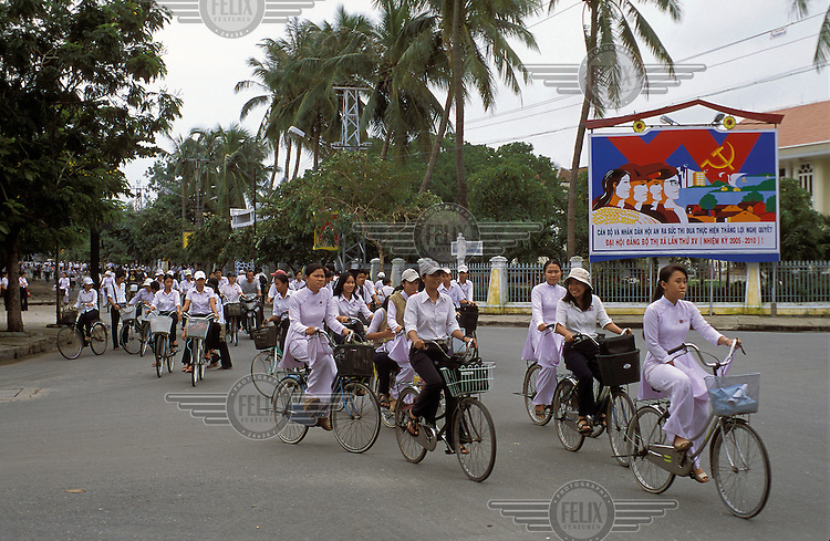 Secondary school girls ride bicycles on their way to school..