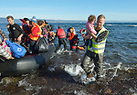 A volunteer carries ashore a small child as refugees land on a beach near Molyvos, on the Greek island of Lesbos, on November 3, 2015, after crossing the Aegean Sea from Turkey. Local and international volunteers welcomed the arriving refugees with food and medical care and dry clothes before the newcomers proceeded on their way toward western Europe. Their boat to Greece was provided by Turkish traffickers to whom the refugees paid huge sums to arrive in Greece.