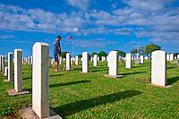 Hawaiian man paying respects at graveside to fallen friend at Makawao Veterans Cemetery, Makawao, Maui