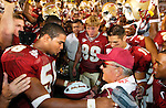 After Florida State's defeat of Wake Forest in Tallahassee on October 25, 2003, FSU linebacker Michael Boulware (L) presents a commemorative football to Florida State head coach Bobby Bowden stating that Bowden became the winningest living football coach and the coach with the most wins in Division 1 with 339 -- passing Joe Paterno. Quarterback Chris Rix (16) is in the background as the rest of the team with helmets raised in a team chant.  (Mark Wallheiser/TallahasseeStock.com)