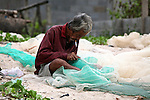 A man repairs a fishing net on the beach in Mui Ne, Vietnam. Nov. 20, 2011.