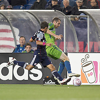 Seattle Sounders forward Nate Jaqua (21) controls the ball as New England Revolution midfielder Ryan Guy (13) closes. In a Major League Soccer (MLS) match, the Seattle Sounders FC defeated the New England Revolution, 2-1, at Gillette Stadium on October 1, 2011.
