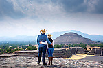 Couple enjoying view of the Pyramid of the Sun from the Pyramid of the Moon.  The pyramids where part of an ancient Mesoamerican city called Teotihuacan in the Valley of Mexico, just outside Mexico City.  It is a UNESCO World Heritage Site.