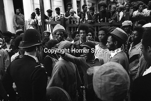 Notting Hill Gate Carnival Riot, London W11 England 1976. A young Rastafarian lets the police know what he thinks.<br /> <br /> Victor Romero-Evans to right of angry youth he is wearing a  woolen hat stretched over a trilby
