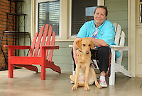 NWA Democrat-Gazette/ANDY SHUPE<br /> Angie Pratt, executive director of Soldier On Soldier Dogs, poses Thursday, May 14, 2015, with Molly, a British Labrador retriever who is being prepared for training as a service dog at the organization's Fayetteville office. The organization is a non-profit organization that provides service dogs for veterans with post-traumatic stress disorder and pairs volunteers with foster dogs to train.