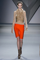 Ros Georgiou walks runway in a Nude organza multi-layer flange harness over nude silk chiffon long sleeve top, and Tangerine melton bermuda short, from the Vera Wang Fall 2012 Vis-a-gris collection, during Mercedes-Benz Fashion Week Fall 2012 in New York.