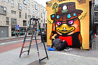 Spray graffiti painter Inkfetish (nickname), working on a small building of Brick Lane, London, UK. Picture by Manuel Cohen