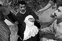 Baghdad, Iraq, April 14, 2003.An old woman collapses and is helped out by neighbours as she fears for the life of her grandson, after an Iraqi hidden artillery depot exploded, levelling 4 houses and projecting shells and debris at several hundred meters. Several other houses caught fire in the incident...