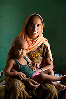 "Shashi Devi (aged 28) sits for a portrait in her house in the village of Shahpurjat, Ghaziabad, Uttar Pradesh, India. While Shashi had a tubectomy done after having 2 sons, Monika, her brother-in-law's wife, is still trying for a son after having 2 daughters. Shashi did the operation because she wanted to ""give her 2 children the best and inflation will make things difficult"", and she believes that a ""small family = happy family"". She has been pushing Monika to get her husband to do an NSV so that Monika's life is not endangered since her previous pregnancies have been complicated. Photo by Suzanne Lee / Panos London"
