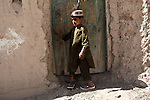 A young boy stands outside the door of a house in Zhor Shar, the old city of Kandahar, Afghanistan. Oct. 7, 2010. DREW BROWN/STARS AND STRIPES