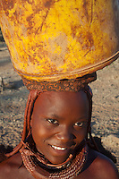 Himba tribe girl carrying water bucket on her head, Namibia.
