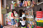 Bunroeun and his sister cousin buy some sweets at a local shop..A Khmer boy learns to play classical violin at the college of Beaux Arts, at the edge of Cambodia's capital, Phnom Penh. He is an orphan and comes from a poor family. His parents died long ago, from AIDS related diseases. He lives with his grandmother and his uncle, and their family. He lives on the top floor of an apartment block, where his family run a textile business, sewing together clothes and ornamental flags from around the world. A dozen young women work in this textile business, and the boy's home space is actually amidst this small factory environment which he shares with them. They eat, work and play together like an extended family or community. Phnom Penh, Cambodia