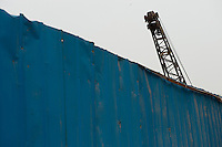 Daytime landscape view of a blue metal fence and a crane at a commercial building construction site on Huang He Dong Lu in the Sānménxiá Shì Húbīn District in Hénán Province.  © LAN