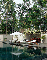 Lunch is served poolside in the shade of a flowering jak tree; the pool is constructed of dark green polished concrete