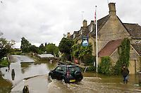 Four wheel drive car drives through flooded road in Swinbrook, Oxfordshire, England, United Kingdom