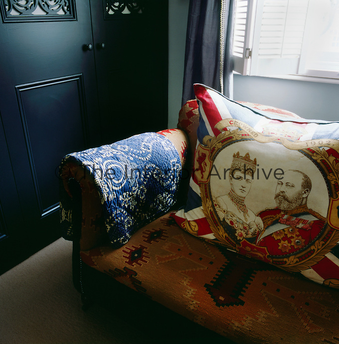 A cushion with an image of King Edward VII is set on a kilim-covered sofa