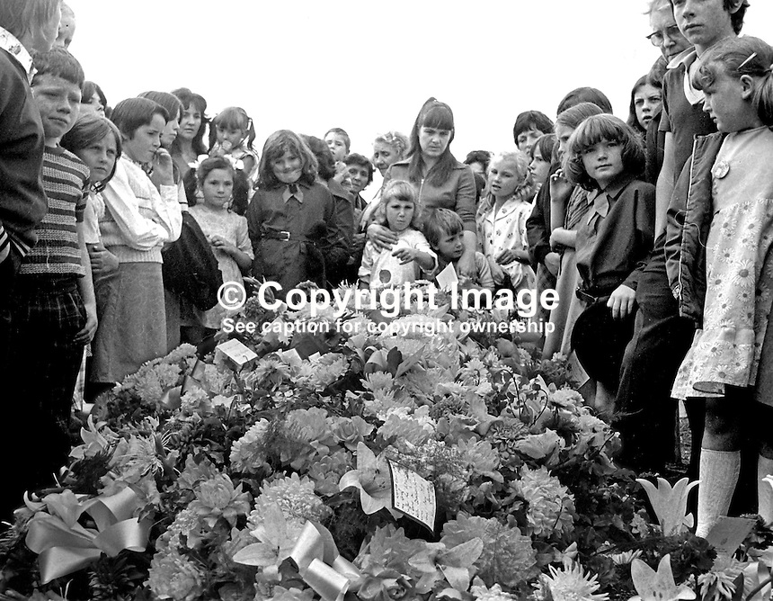 Mourners view the floral tributes at the grave of the three Maguire children, Joanne, 8 years, John, 2 years, and Andrew, 6 weeks, who died as a result of one of the most tragic and horrific incidents of the N Ireland Troubles on 10th August 1976. A car driven by Daniel Lennon, aka Danny Lennon, member, Provisional IRA, mounted the pavement and ploughed into the Maguire family. Lennon died at the wheel having been shot by British soldiers in hot pursuit. The incident gave rise to the birth of the Peace People organisation led by Mairead Corrigan, aunt of the dead children, and another local woman,Betty Williams. 197608130371e.<br /> <br /> Copyright Image from Victor Patterson, 54 Dorchester Park, Belfast, UK, BT9 6RJ<br /> <br /> t1: +44 28 9066 1296 (from Rep of Ireland 048 9066 1296)<br /> t2: +44 28 9002 2446 (from Rep of Ireland 048 9002 2446)<br /> m: +44 7802 353836<br /> <br /> e1: victorpatterson@me.com<br /> e2: victorpatterson@gmail.com<br /> <br /> The use of my copyright images is subject to my Terms &amp; Conditions.<br /> <br /> It is IMPORTANT that you familiarise yourself with them. They are available on my website at www.victorpatterson.com.<br /> <br /> None of my copyright images may be used on a website unless they are visibly watermarked, i.e. &copy; Victor Patterson within the body of the visible image. Metadata denoting my copyright must NOT be deleted. <br /> <br /> Web use (maximum size - 400 kb) is extra at currently recommended NUJ rates.