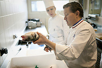 Chef Eric Robert (foreground) prepares a fish as a student looks on during a class at the Ecole Superieure de Cuisine Francaise Gregoire Ferrandi cooking school in Paris, France, 18 December 2007.