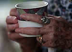 Close up of hands of elder holding mug of coffee.