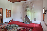 Living room with chimney representing a typical traditional Ottoman house in the Gjirokastra Ethnographic Museum, on the site of the childhood home of Enver Hoxha, Albania's communist dictator 1944-85, Gjirokastra, Albania. The museum building was constructed in 1966 after the original house was destroyed by fire. Gjirokastra was settled by the Greek Chaonians, the Romans and Byzantines before becoming an Ottoman city in 1417. Its old town was listed as a UNESCO World Heritage Site in 2005. Picture by Manuel Cohen